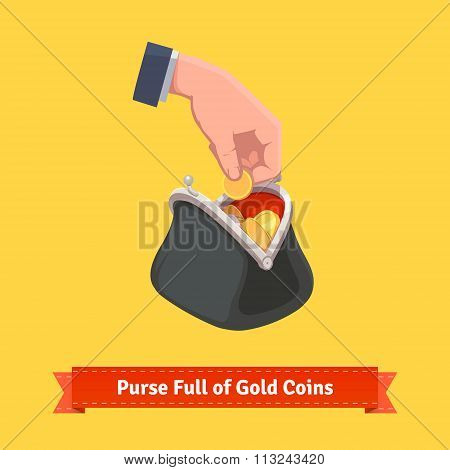 Human hand putting coin to a retro money purse