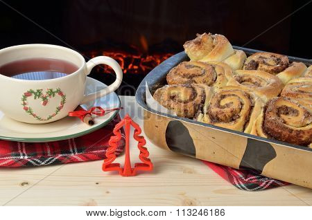Pan With Fresh Cinnamon Rolls With Tea By The Fireplace