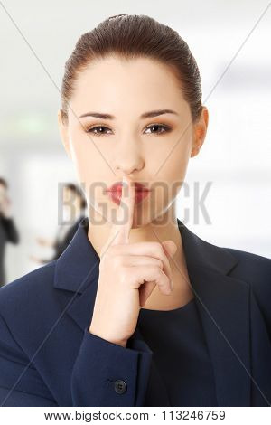 Hush. Businesswoman with finger on her lips gesturing for quiet