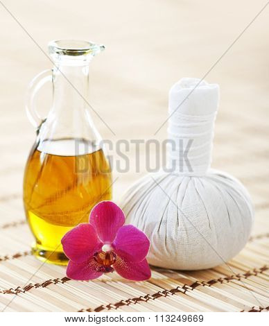 Spa aromatherapy composition with fragrant oil, orchid and ball on bamboo mat over isolated background.