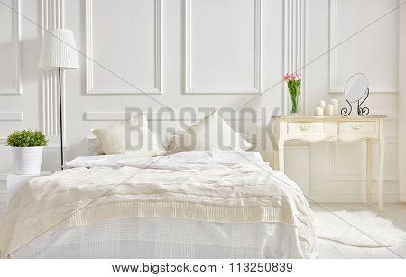 bedroom in soft light colors. big comfortable double bed in elegant classic bedroom