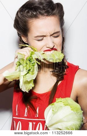 Daring funny girl with braids and red lips, emotional eating cabbage. Beauty emotion face.