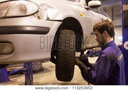 Auto Mechanic Repairs A Car In A Garage.