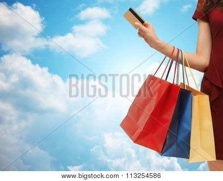 close up of woman with shopping bags and bank card