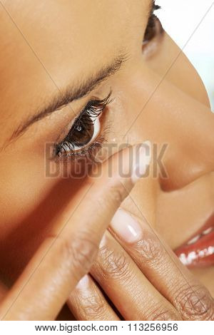 Young woman putting contact lens in her eye