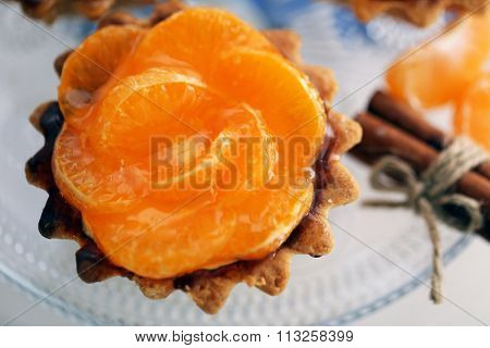 Sweet cake with tangerines on plate, close up