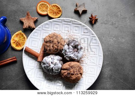 Chocolate balls with dried orange and cinnamon on table