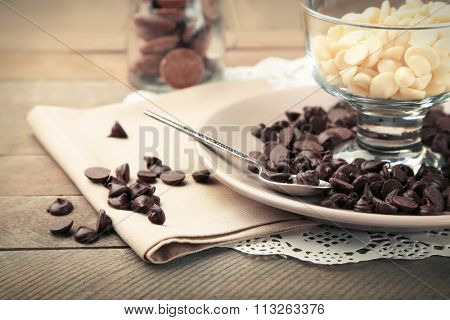 Chocolate morsels in glass bowl on wooden background