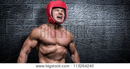 Angry boxer with headgear against grey brick wall