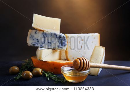 Different kinds of cheese, honey and olives on the table, close up