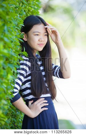 Portrait Of Younger Asian Teen With Happiness Emotion And Smiling Face In Green Park
