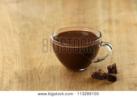 Cup of cacao with chocolate on wooden table