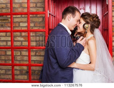 Young wedding couple posing in red english call-box