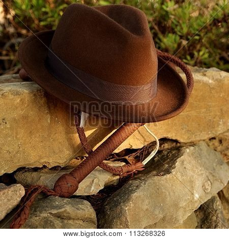 Fedora hat and bullwhip on a stone wall