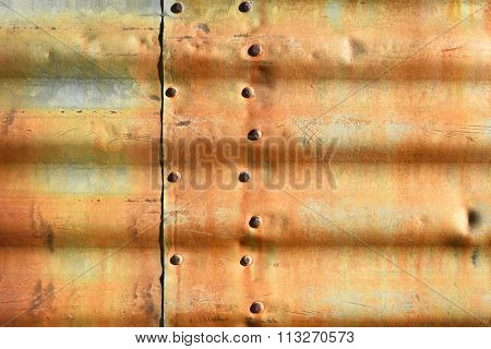 Rusty corrugated metal with rivets.