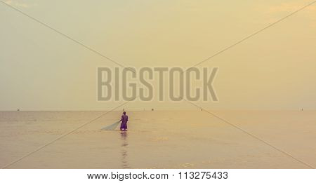 Fisherman With Fishing Net In The Sea In Thailand