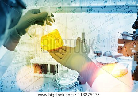 Researcher Is Dropping The Reagent Into Test Tube In Laboratory, With Chemical Table Background.