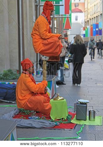 Street performers are showing a magical trick, levitation in the air