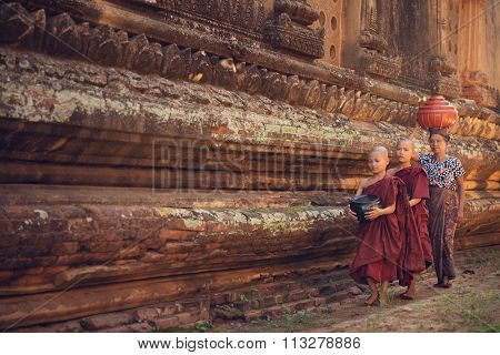 Young Buddhist novice monks walking morning alms in Old Bagan, Myanmar