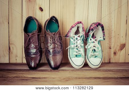 Men's Brown Shoes And Sneakers On The Wooden Floor