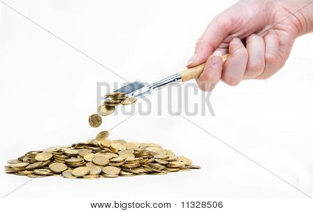 Hand With Shovel Strewing Coins On Pile