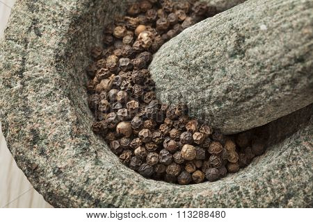 Traditional mortar and pestle with dried black pepper close up