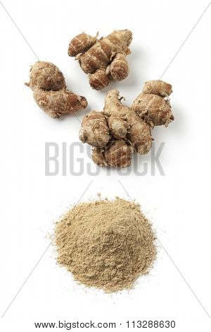 Fresh kencur roots and ground kencur powder on white background