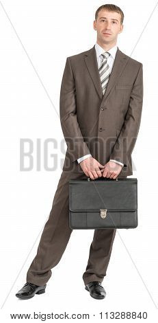 Happy businessman standing with suitcase