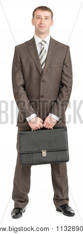 Smiling businessman standing with suitcase