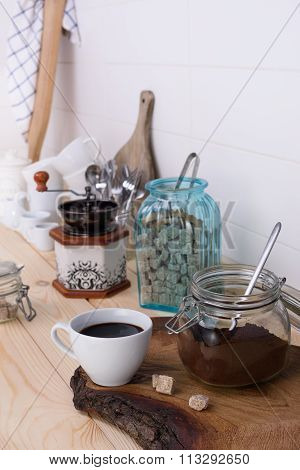 Ground coffee blend and freshly brewed coffee with cane sugar. Wooden buffet counter with utensil.
