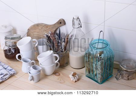 Still life of coffee cups and utensil on a wooden bar counter. White background, copy space.