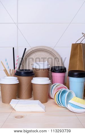 Coffee and tea cups for on the go. Paper and thermo mugs for hot or cold drinks, wooden bar counter