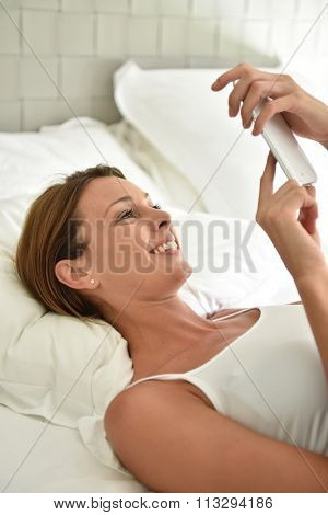 Woman laying on bed and using smartphone