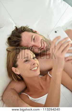 Couple laying in bed using smartphone