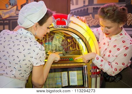 Two girls in retro dress press button on old-fashion musical machine in bar