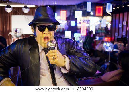 Waxwork singer in black suit and hat in bar interior