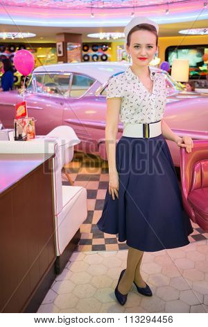 Beautiful young woman in retro dress in bar with pink car.