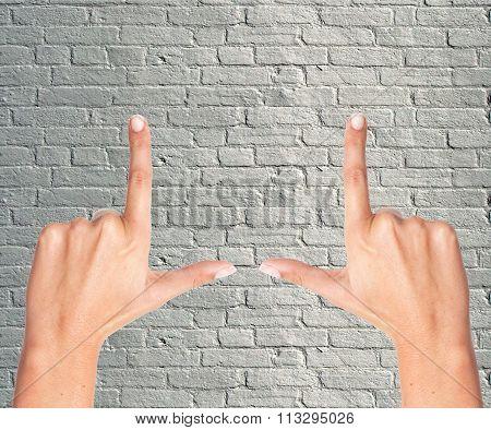 Finger Frame Over Grey Brick Wall