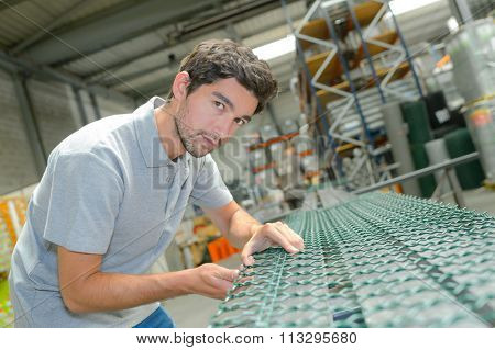 Man connecting linkages on conveyor belt