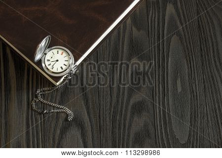 Old silver pocket watch and a book lying on the wooden table. Top view
