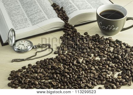 The book a cup of coffee coffee beans and a pocket watch on a wooden table