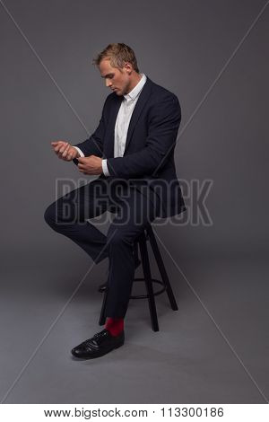elegant young fashion man in tuxedo sitting on the chair
