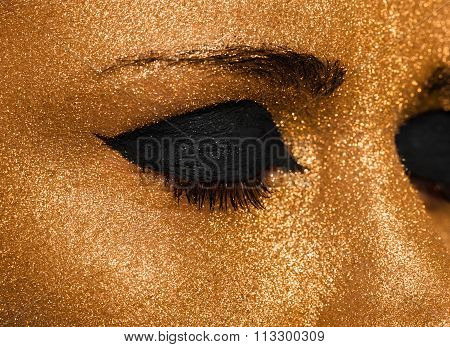 Golden Woman's Face Closeup. Futuristic Gilded Make-up. Painted Skin