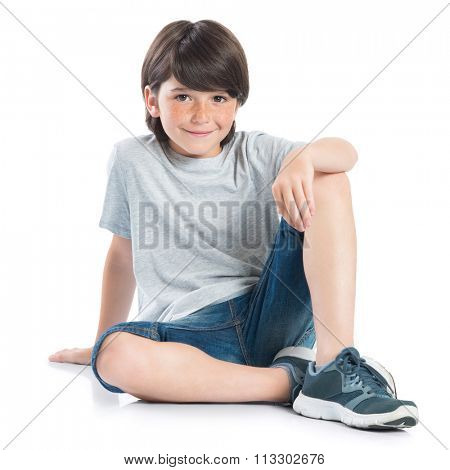 Closeup shot of smiling little boy sitting on white background. Adorable child in casual looking at camera. Happy cute boy sitting on floor and looking at camera.
