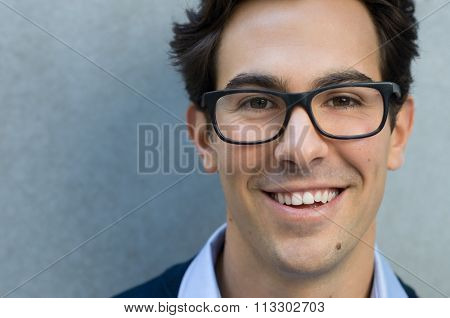 Young man smiling and looking at camera wearing glasses. Portrait of a happy handsome young man wearing spectacles with grey background. Close up of cool trendy man with glasses and copy space.