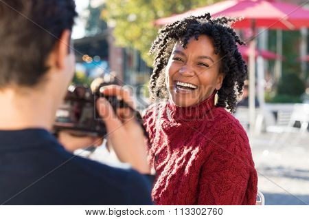 Young beautiful african woman posing for a photo. Boyfriend clicking a picture with camera of an smiling girlfriend. Happy woman having photos clicked by a photographer outside. Man taking a picture.