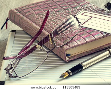 Pen And Glasses Lying On The Notepad