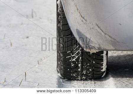 Snow-covered road in winter ,  car on a dangerous road.  Tire in snow.