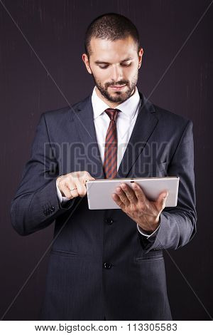 Executive man using a digital tablet against grunge background