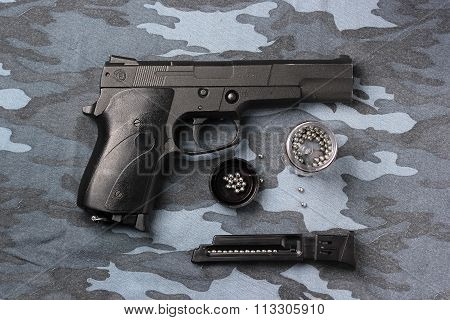 Black Pneumatic Pistol On A Camouflage Background.